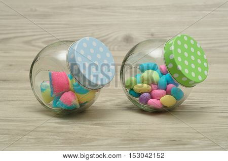Jars filled with candy displayed on a wooden background