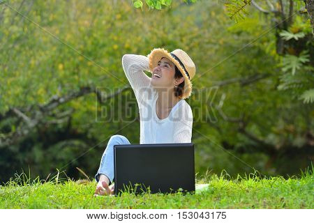 Happy middle aged woman smiling a perfect smile and white teeth and using laptop computer in the park