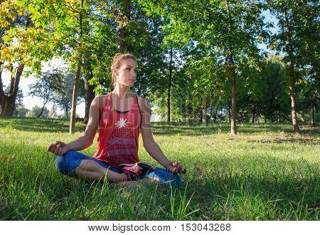 Sport woman enjoying meditation in a city park sitting on the green grass