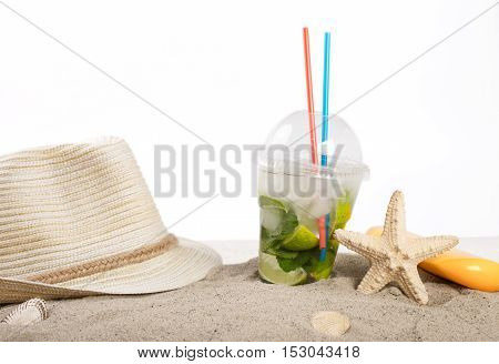 Summer cocktail with beach accessories in the sand on a white background