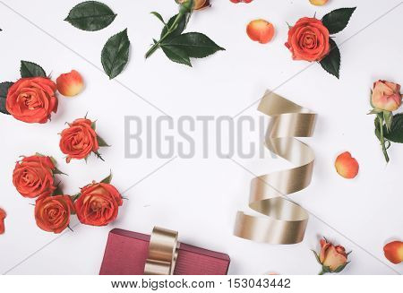 Frame of red roses and gift with golden ribbon on white background top view