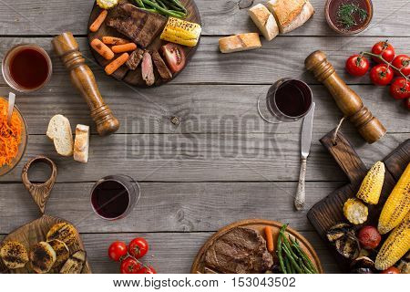 Frame of different food cooked on the grill. Grilled vegetables grilled steak and red wine. Top view