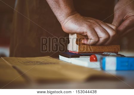 close-up of unrecognizable worker with wooden stamp marking coffee bags