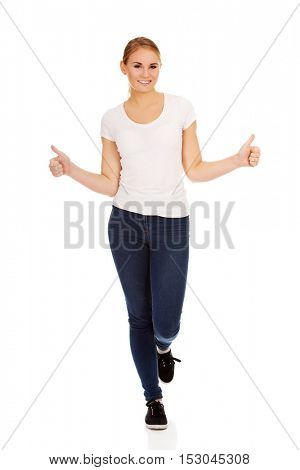 Young happy woman gesturing thumbs up