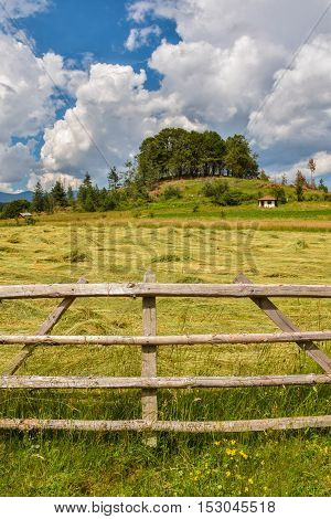 Small countryside house with a wooden fence in the foreground