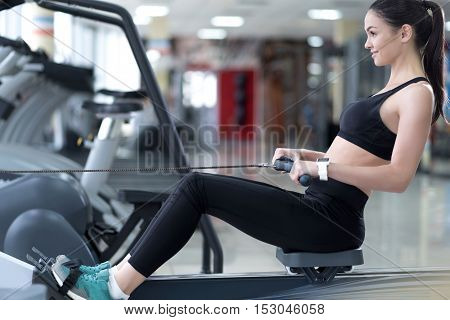 Explore your body. Delighted happy young woman doing her exercises and improving her muscles while training in a gym.