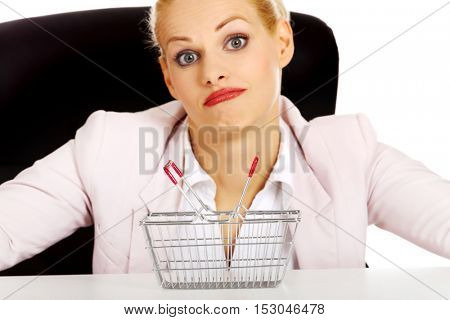 Surprised business woman sitting behind the desk with small shopping basket