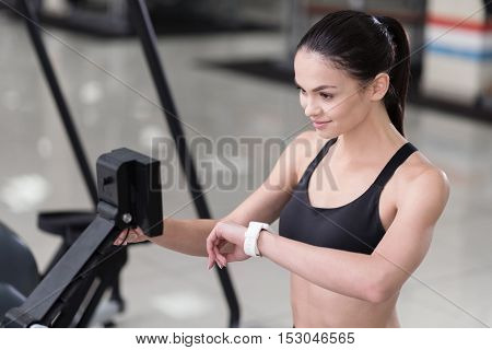 Control your body. Young pretty active woman using scales and smart watch while controlling her weight and pulse after having training.