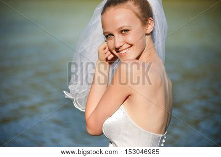 Stunning young bride with veil  near water outdoors