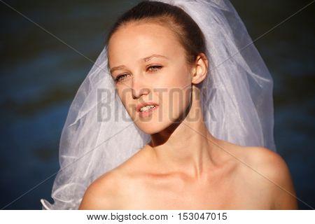 Modern bride close -up near water outdoors