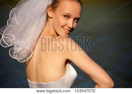 Young bride glances over her shoulder outdoors