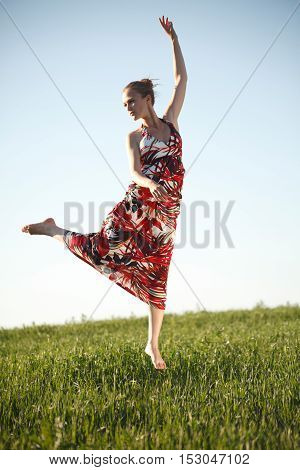 Young slim beauty jumping high on the field