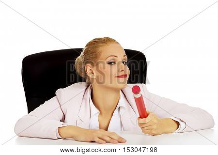 Young business woman sitting behind the desk and holding big pen