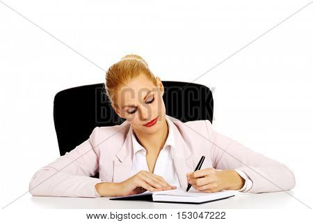 Pensive business woman taking notes behind the desk