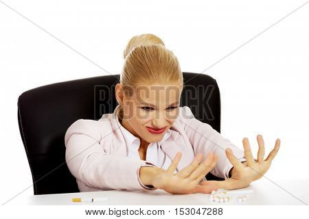 Business woman sitting behind the desk don't want to smoke