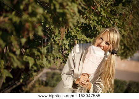 Blondie girl is eating candy-floss in early autumn park.Selective focus on the background