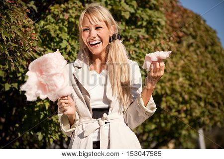 Happy girl in early autumn park with candy-floss