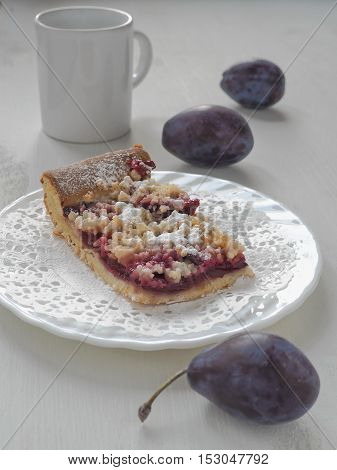 Piece of Bavarian plum pie on white plate with milk and fresh plums. Selective focus.