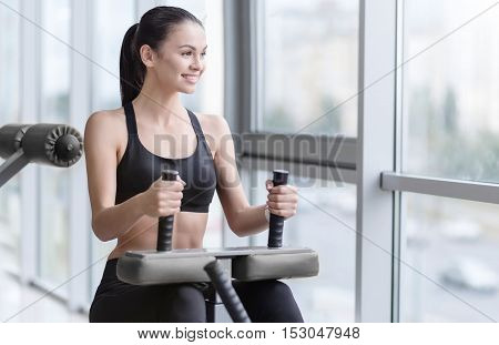 Working out. Slim delighted young girl using a treadmill and training while spending time in a gym.