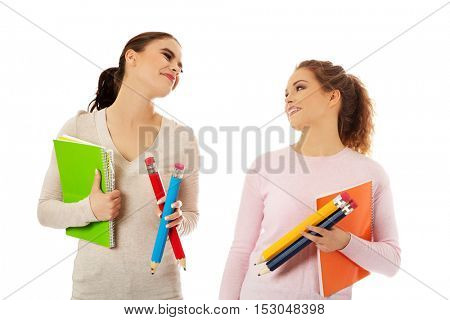 Young happy students posing over white background.