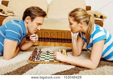 Focused happy couple playing chess on the floor