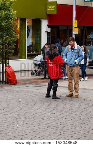 NOTTINGHAM ENGLAND - OCTOBER 19: Female Shelter street fundraiser talking to a man. In Nottingham England. On 19th October 2016.