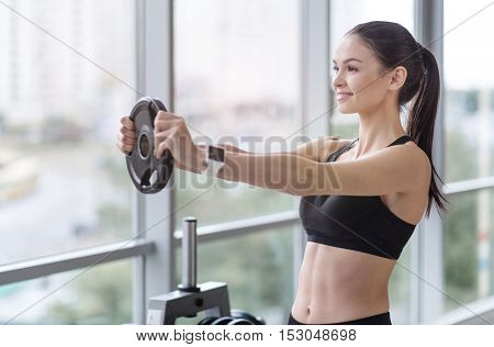 Keep going. Athletic pretty young girl doing fitness exercises and having workout enjoying time in a gym.