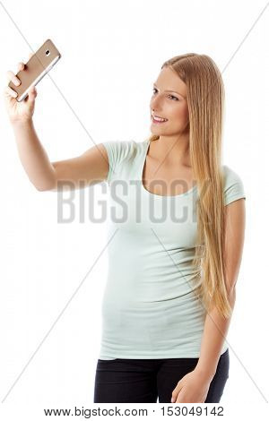 Smiling young girl making selfie photo isolated on a white.