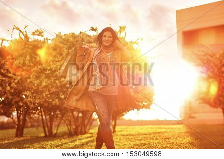 Cheerful pregnant woman with shopping bags in the garden in bright sunny day, autumn season sale, doing purchase for a baby, happy pregnancy period