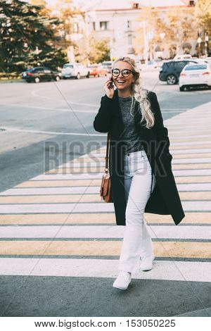 Blond woman wearing black coat, white pants, hipster glasses walking on city street and talking by phone on crosswalk. Fall casual fashion, elegant everyday look. Plus size model, lifestyle photo.