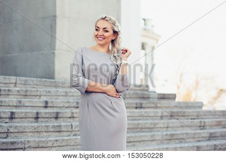 Young blond woman wearing elegant fashion dress walking on the city street. Plus size model.