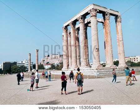 Athens, Greece - October 16, 2016: Tourists near Temple of Olympian Zeus and Acropolis Hill, Athens, Greece