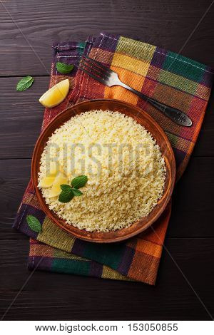 Couscous with mint and lemon in plate on wooden rustic table from above. Copy space for text.