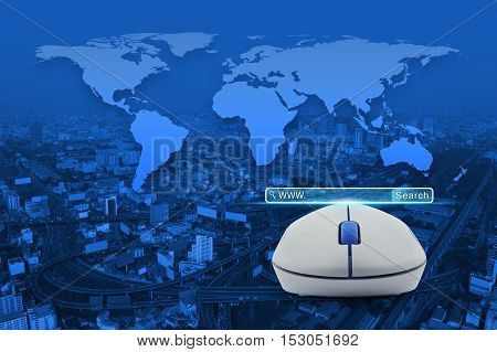 Wireless computer mouse with search www button over city tower street and expressway Searching system and internet concept Elements of this image furnished by NASA
