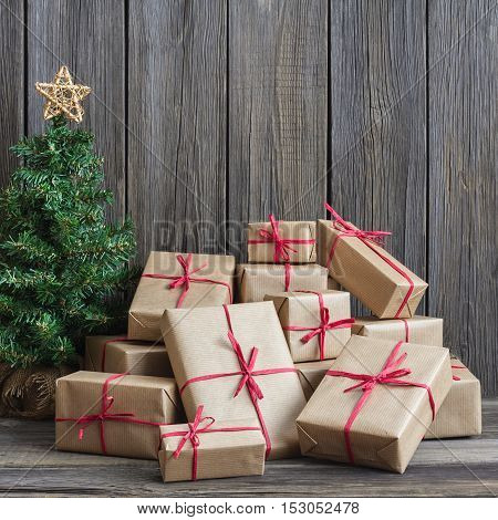 Vintage packages and Christmas tree against the background of the old wooden boards