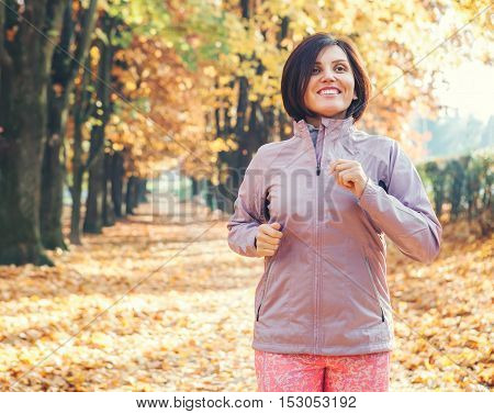Running smiling woman portrait in autumn park
