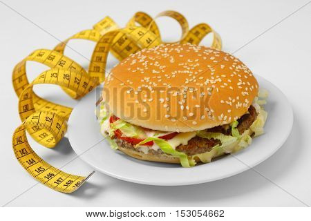 Hamburger with centimeter on white plate