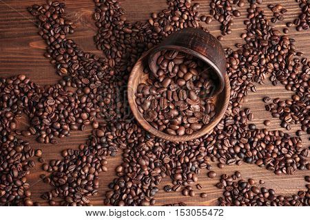 Bowls with coffee beans on wooden background