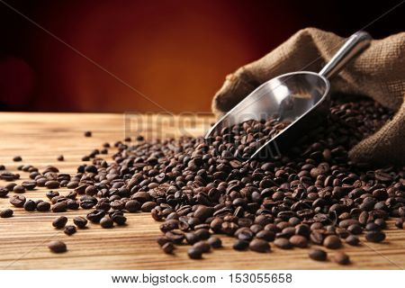 Coffee beans, sack and scoop on wooden table against dark background, close up view