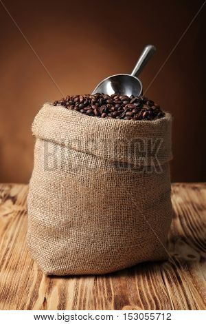 Sack with coffee beans and scoop on wooden surface against brown background