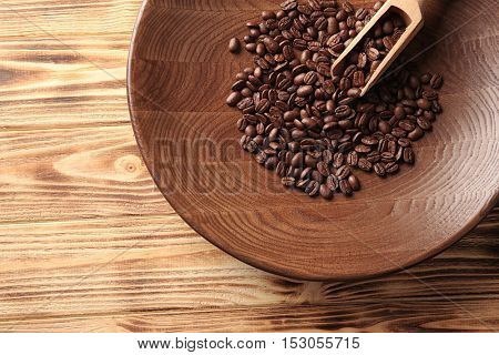 Plate with coffee beans and scoop on wooden background