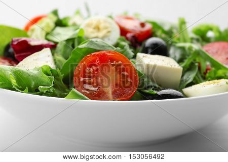 Bowl of fresh mixed salad leaves with tomatoes closeup