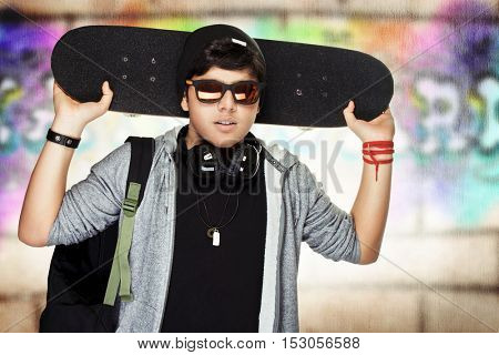 Stylish teen boy with skateboard, urban graffiti wall background, active handsome guy listening music, modern life of young people