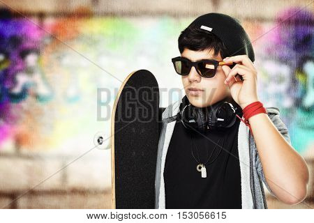 Portrait of a handsome skateboarder wearing sunglasses and stylish hat outdoors, active stylish teen