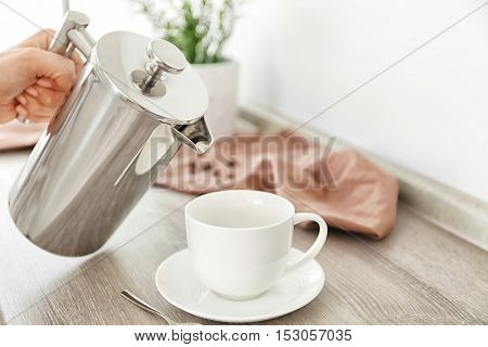 Fresh coffee pouring from pot into cup