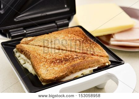closeup of two sandwiches filled with ham and cheese toasted in an electrical sandwich toaster
