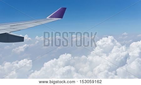 View from window with wing of airplane flying above the clouds