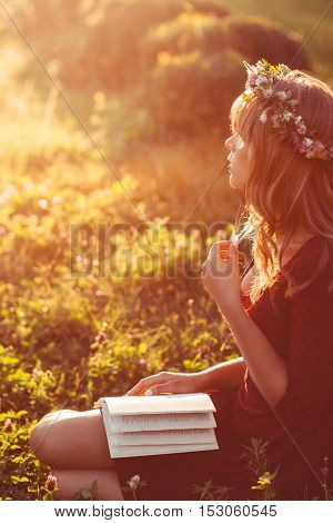 Profile of girl in wreath with book, sun flare effect. Free space on green meadow, attractive woman relaxing in nature during sunset. Rest, education, unity with nature concept