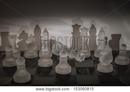 Dark mysterious view of a chess board with illuminated fallen king.