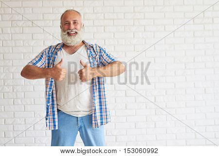 Smiling stylish senior dressed in jeans and checkered shirt show thumbs up with both hands, white brick wall in background
